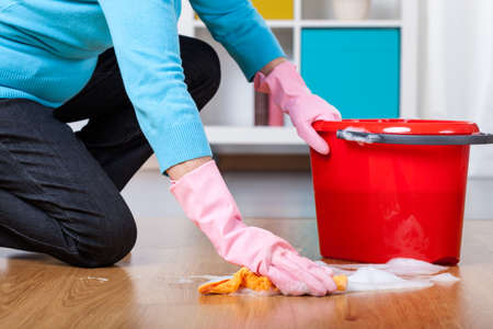 house chores: Elderly woman kneeling, doing floor cleaning at home