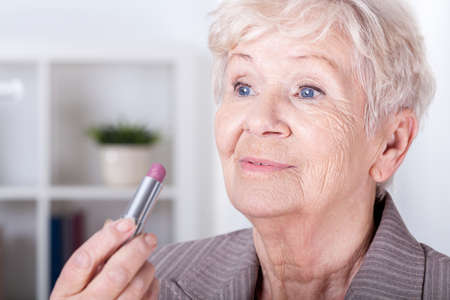 Elegant elderly woman putting on pink lipstick photo