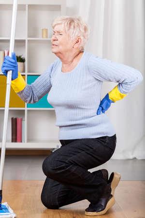 dolor espalda: Mujer mayor que come el dolor de espalda durante la limpieza