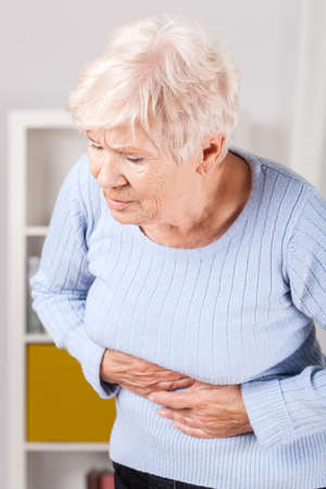stomachache woman: Portrait of elderly woman having stomachache at home