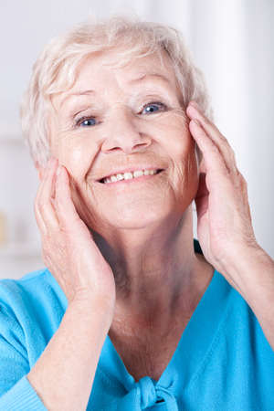 Smiley elderly woman doing her skin care photo