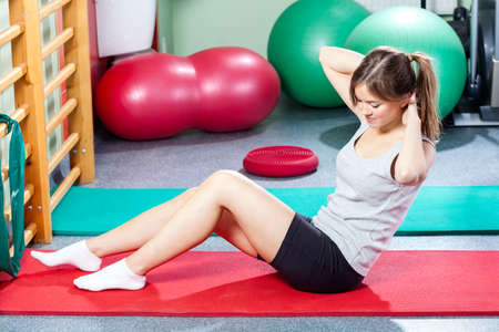 Young girl doing crunches on gym mat photo