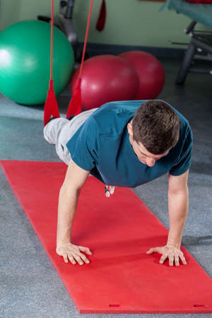 aerobic treatment: Young man exercising in suspension on gym mat
