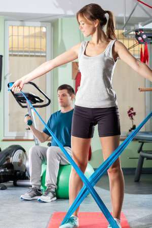 Young man and woman doing exercise, vertical photo