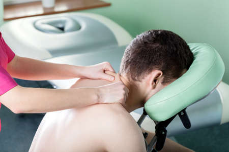 Close-up of man receiving shoulder massage, horizontal photo
