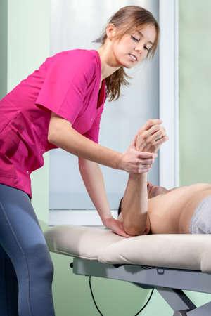 codo: Joven fisioterapeuta tratar el codo de tenista femenina, vertical