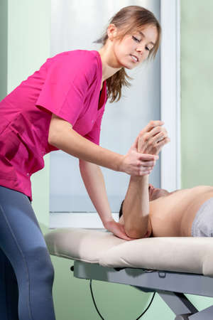 contusion: Young female physiotherapist treating tennis elbow, vertical