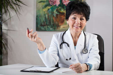 professionalist: A smiling middle-aged female doctor sitting by her desk at the surgery Stock Photo