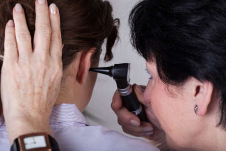 A closeup of a doctor examining her patients ear photo