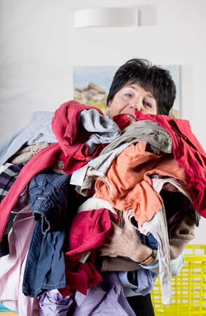A woman holding a pile of dirty clothes to wash photo