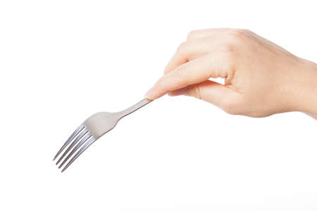 Hand holding silver fork and going to eat something
