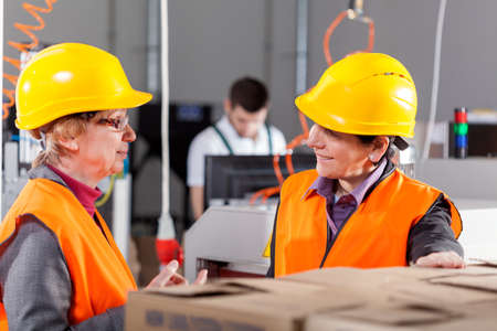 production area: Female employees discussing at production area, horizontal Stock Photo