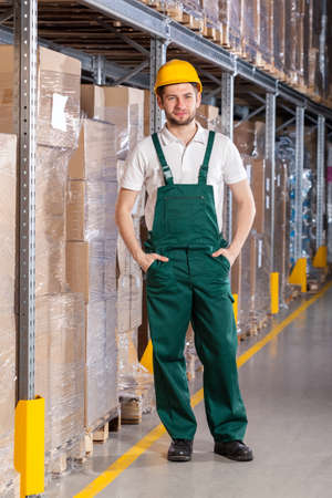 Smiling warehouseman during standing in storage, vertical photo
