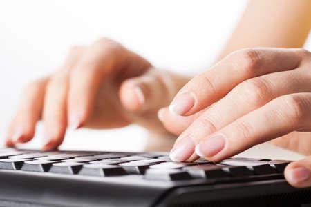 Woman hands writting on black computer keyboard photo
