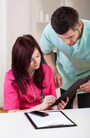 medical notes: Doctors making medical notes at work, vertical