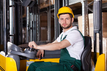 warehouseman:  Storehouse employee during driving on forklift in warehouse Stock Photo
