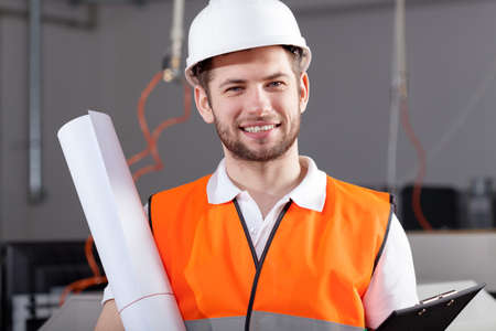 warehouseman: Engineer standing in warehouse, holding new project Stock Photo