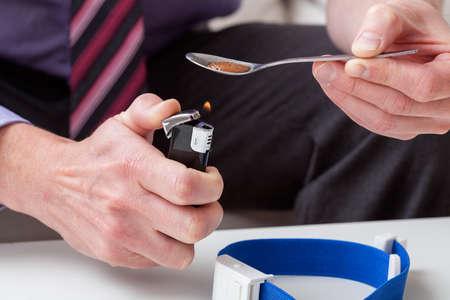 sobredosis: El hombre se está calentando drogas en cuchara Foto de archivo