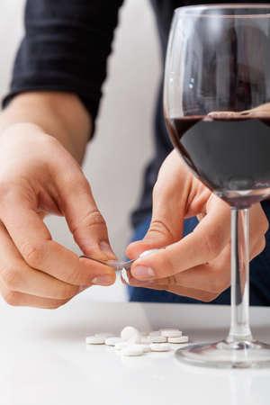 tomando alcohol: La mujer est� tomando pastillas y bebiendo alcohol