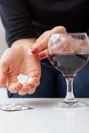Woman is taking pills and drinking alcohol photo
