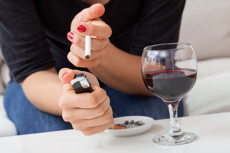 addiction drinking: Woman with cigarette and glass of red vine