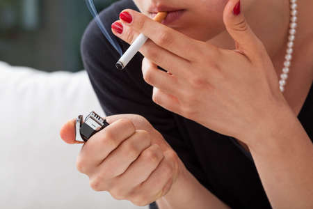 Woman is lighting cigarette with black lighter Stock Photo