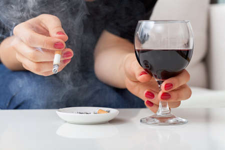 Woman is smoking cigarette and drinking alcohol