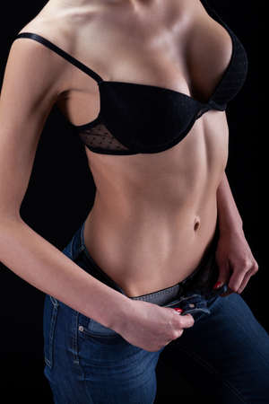 Sexy woman wearing bra and jeans, vertical photo