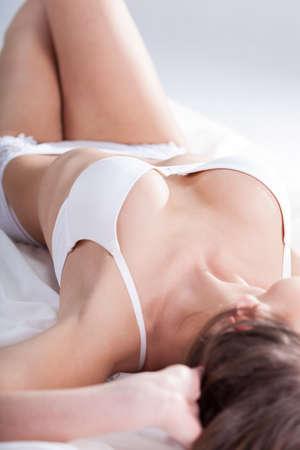 corps femme nue: Femme en sous-v�tements sexy au lit, vertical Banque d'images