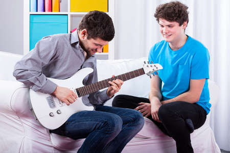 boy playing guitar: Man showing to his friend his new electric guitar