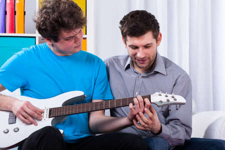 Boy learning to play on electric guitar on private lesson Stock Photo