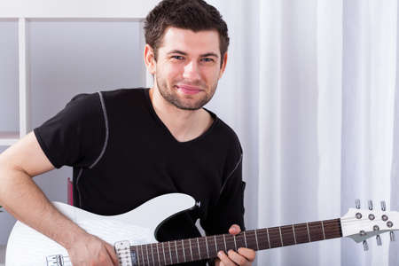 showbusiness: Young musician has to practise  playing on elecrtic guitar