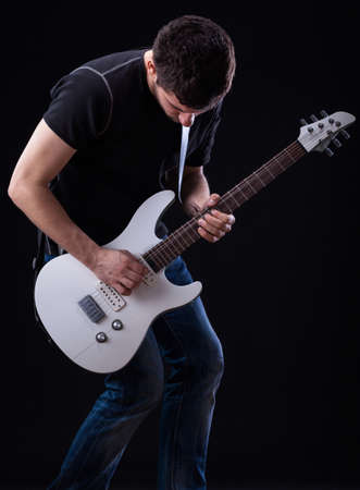 play popular: Guitarist from rockband during his solo on a stage