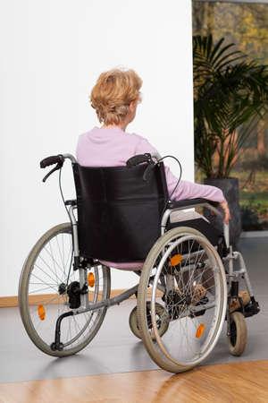 Elderly lady during sitting on wheelchair, vertical photo