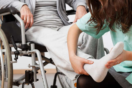 physiotherapist: Disabled person during rehabilitation with her nurse Stock Photo
