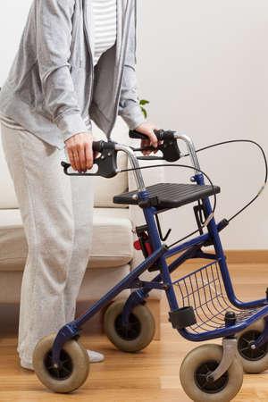 Gehandicapte dame tijdens het lopen met rollator, verticale