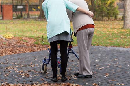 Verpleegkundige en gehandicapten met rollator aan de buitenkant