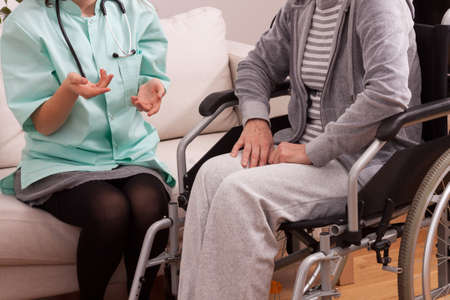 Nurse talking with disabled patient at home photo