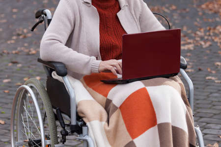 netbook: Modern disabled lady on wheelchair using netbook