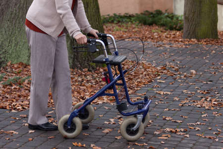 Disabled person walking with walker outdoors, horizontal photo