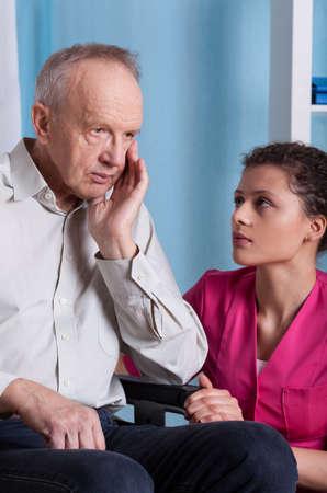 Elderly man on wheelchair and nurse, vertical Stok Fotoğraf