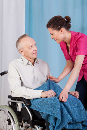 View of a nurse caring about disabled man photo