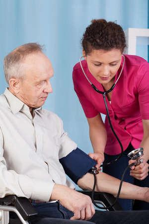 Vertical view of a nurse measuring patients pressure  Zdjęcie Seryjne