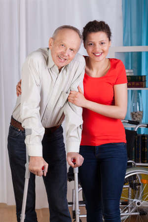 Disabled man standing with his nurse, vertical photo