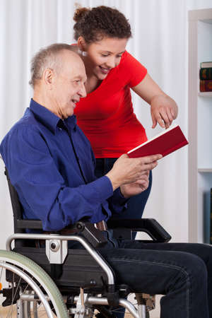 Nurse and disabled man reading book, vertical photo