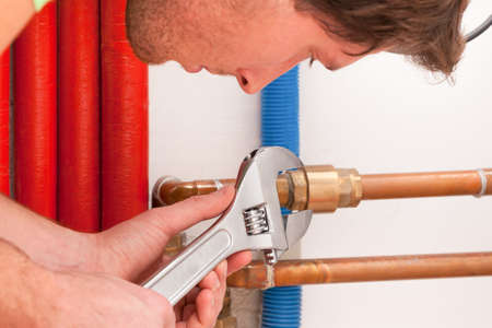 Closeup of a handyman using wrench for pipes photo