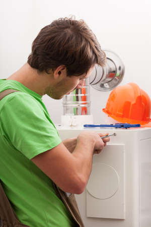 Handyman repairing central heating in boiler room Stock Photo