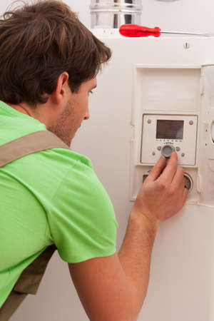 Man changing temperature setting on central heating boiler