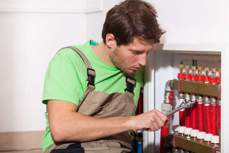 Young repairman fixing valves in his home photo