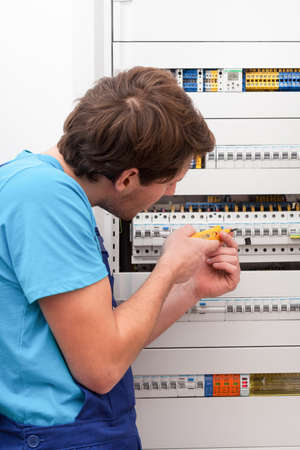 fusebox: Young repairman checking voltage on switchboard in boiler room